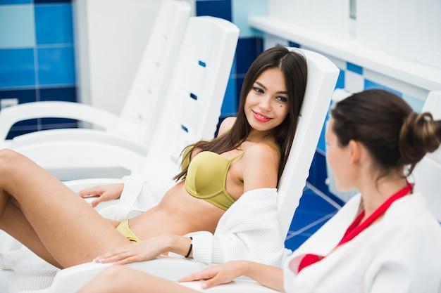 Przyjaciele ubrani w szlafroki i bikini relaksują się w spa przy basenie