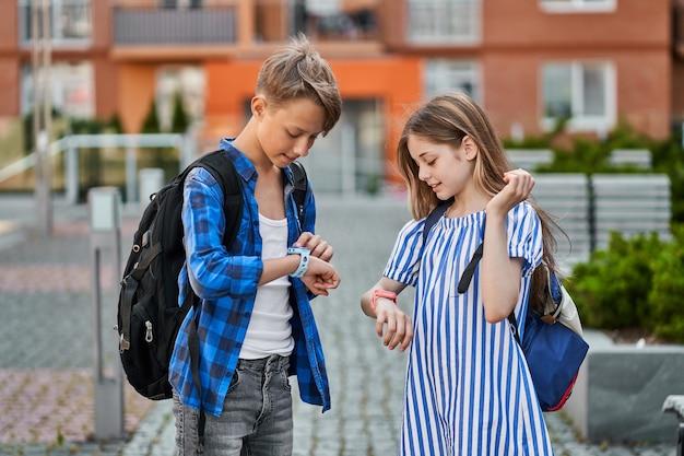 Przyjaciele ucznia chłopiec i dziewczynka gra inteligentny zegarek w pobliżu szkoły.