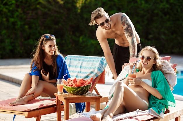 Przyjaciele uśmiechają się, jedzą arbuza, piją koktajle, relaksują się w pobliżu basenu
