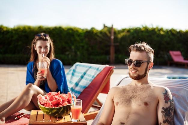Przyjaciele uśmiechają się, odpoczywają, piją koktajle, leżą w pobliżu basenu