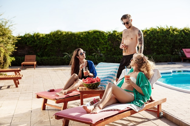 Przyjaciele uśmiechają się, opalają, piją koktajle, leżą w pobliżu basenu