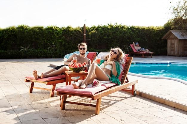 Przyjaciele uśmiechają się, piją koktajle, leżą na leżakach w pobliżu basenu