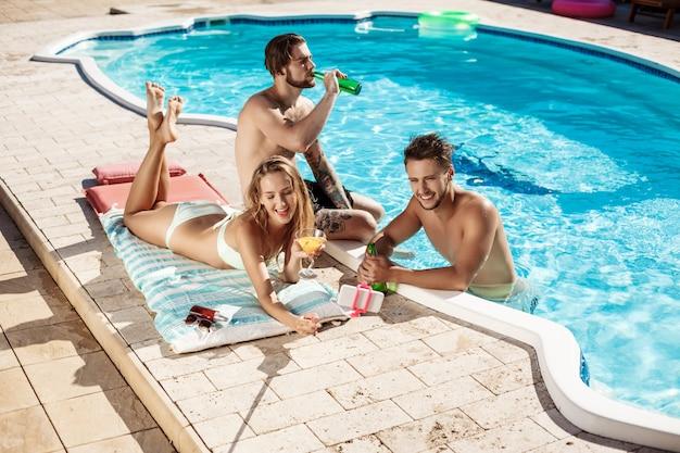 Przyjaciele uśmiechają się, robią selfie, piją koktajle, relaksują się w pobliżu basenu