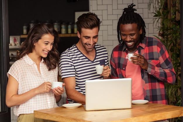 Przyjaciele używa laptop i trzyma filiżanki kawy