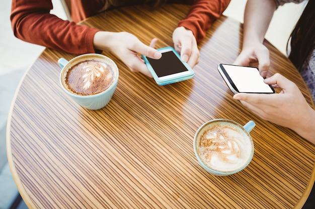 Przyjaciele używa smartphone i ma kawę w sklep z kawą
