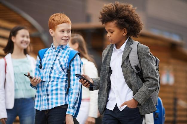 Przyjaciele używają telefonów komórkowych na zewnątrz