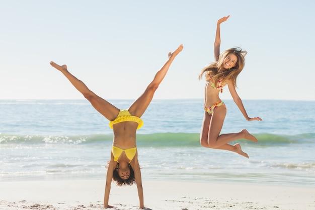 Przyjaciele w bikini skoki i robi handstand