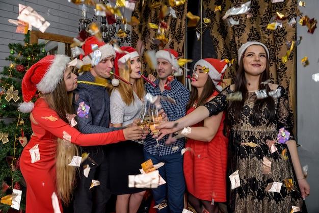 Przyjaciele w czapkach mikołaja pozują w świątecznym studiu