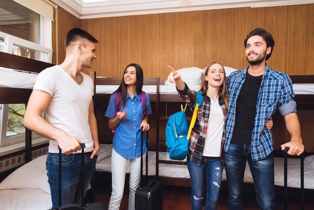 Przyjaciele w hostelu. mężczyźni mają walizki, kobiety mają plecaki.