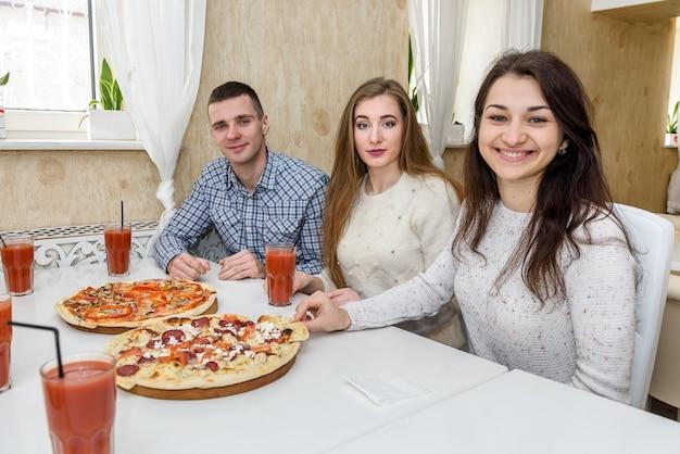 Przyjaciele w kawiarni, jedzenie pizzy i pozowanie do aparatu
