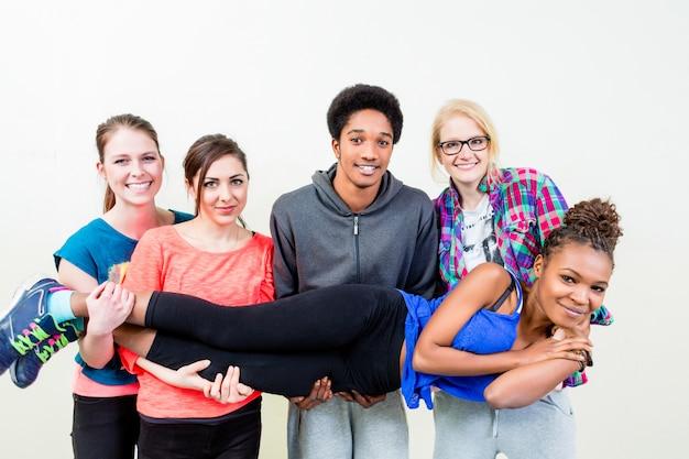 Przyjaciele w klasie tańca, niosąc kobietę na rękach