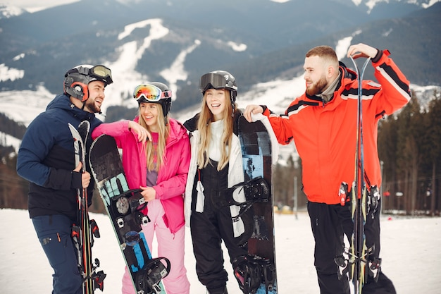 Przyjaciele w kombinezonach snowboardowych. sportowcy na górze z snowboardem. na horyzoncie ludzie z nartami w rękach. koncepcja sportu