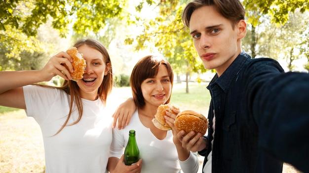 Przyjaciele w parku robią selfie, jedząc hamburgery i piwo