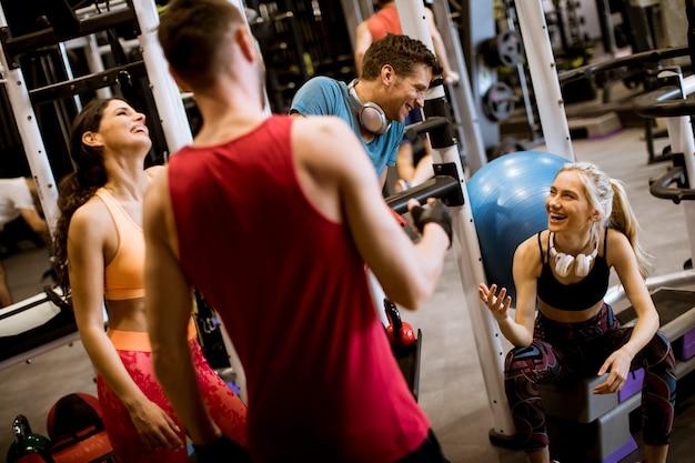 Przyjaciele w sportowej rozmawiają razem stojąc w siłowni po treningu