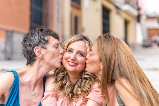 Przyjaciele w średnim wieku wspólnie spędzają czas i dobrze się bawią. dwóch przyjaciół całujących innego przyjaciela w środek w policzek.