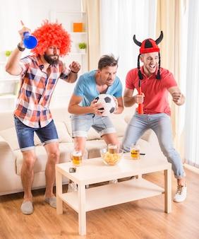 Przyjaciele w strojach piłkarskich emocjonalnie oglądają piłkę nożną.