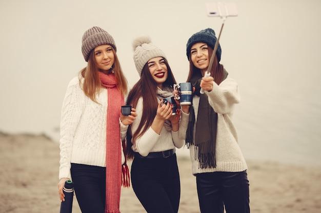 Przyjaciele w zimowym parku. dziewczyny w robionych na drutach kapeluszach. kobiety z termosem i herbatą.