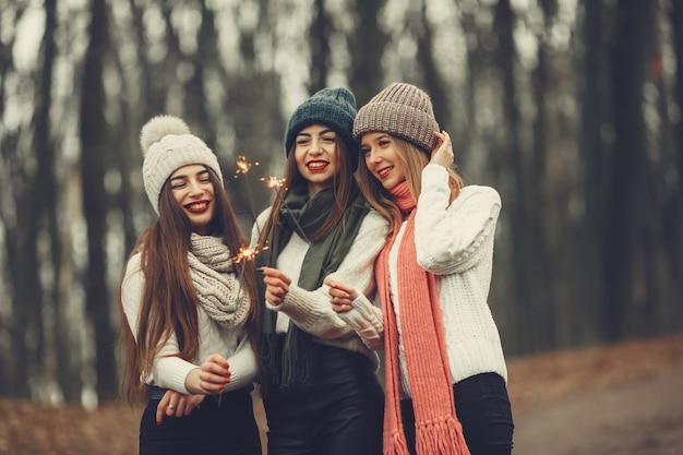 Przyjaciele w zimowym parku. dziewczyny w robionych na drutach kapeluszach. kobiety z zimnymi ogniami.