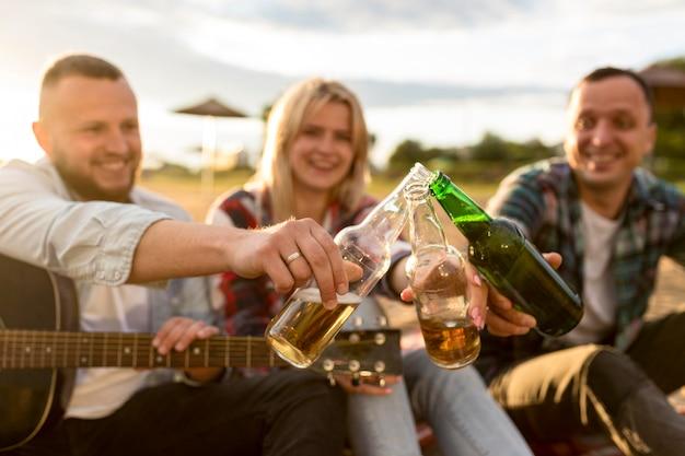 Przyjaciele wiwatują przy butelkach piwa