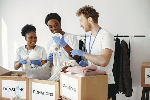 Przyjaciele wolontariusze układają pudełka. inspekcja pomocy humanitarnej. darowizny dla ubogich.