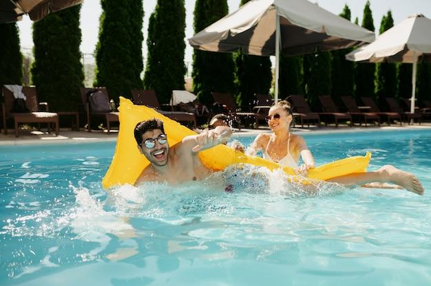 Przyjaciele wygłupiają się na materacu w basenie. szczęśliwi ludzie bawią się na letnie wakacje, impreza świąteczna przy basenie na świeżym powietrzu. jeden mężczyzna i dwie kobiety wypoczywają w ośrodku?