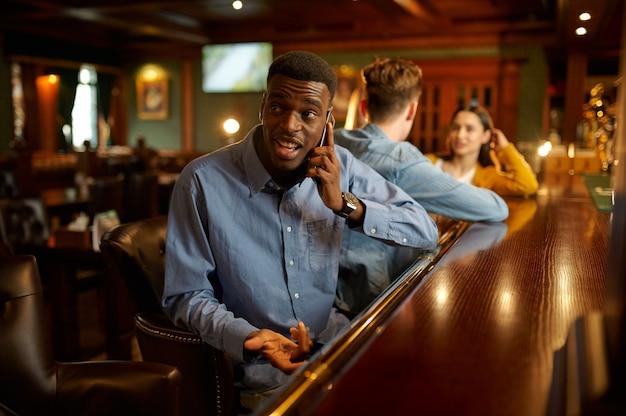 Przyjaciele wypoczywają przy ladzie w barze, kluby nocne