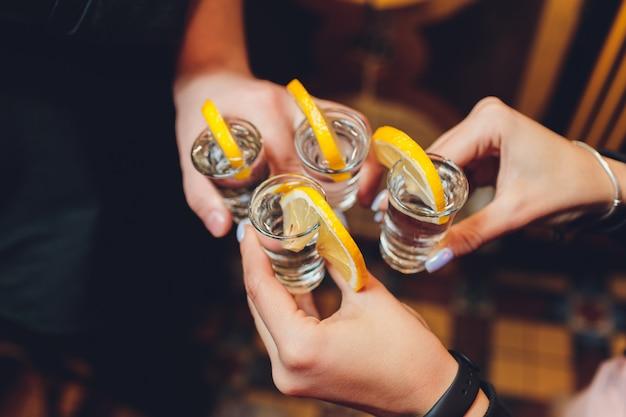 Przyjaciele wznosi toast z strzałów szkłami nad stary drewniany stołowy czarny tło.