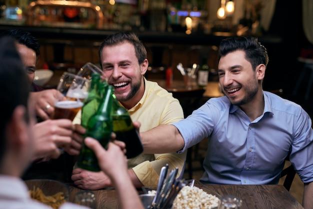 Przyjaciele wznoszą toast w pubie