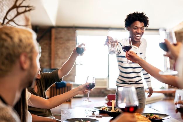 Przyjaciele wznoszący toast na imprezie