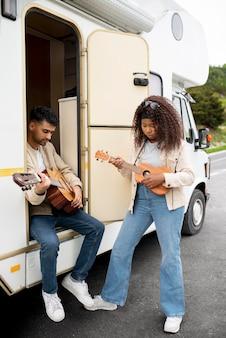 Przyjaciele z gitarą na zewnątrz w pełnym ujęciu