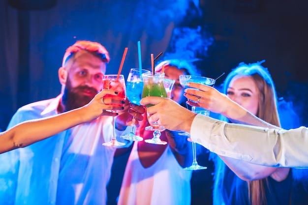 Przyjaciele z koktajlami piją na imprezie.