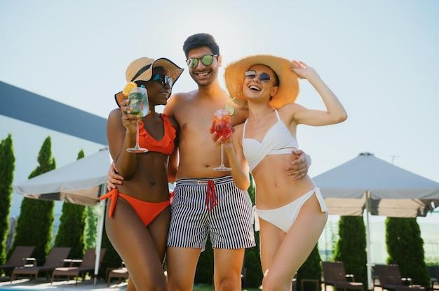 Przyjaciele z koktajlami pozują na basenie w hotelu. szczęśliwi ludzie bawią się na letnie wakacje, impreza świąteczna przy basenie na świeżym powietrzu. jeden mężczyzna i jedna kobieta opalają się
