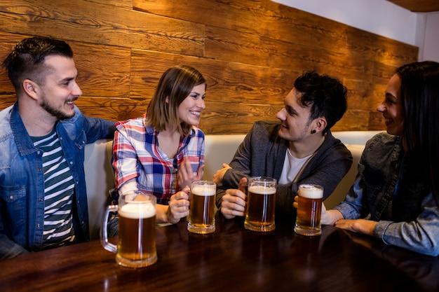 Przyjaciele z kufle do piwa przy stole w restauracji