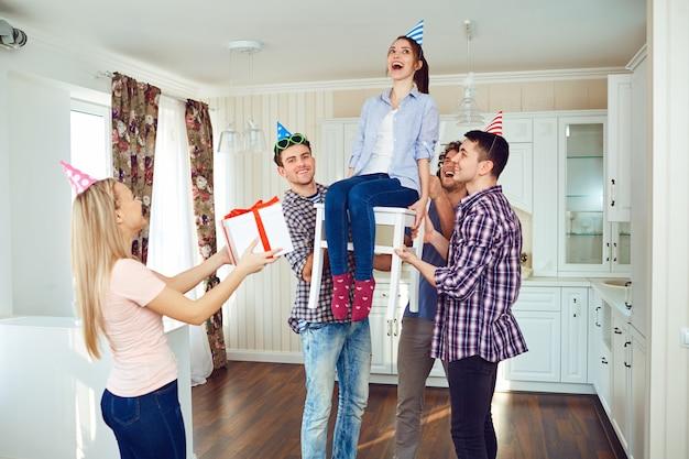 Przyjaciele z tortem obchodzi urodziny na imprezie w pokoju.