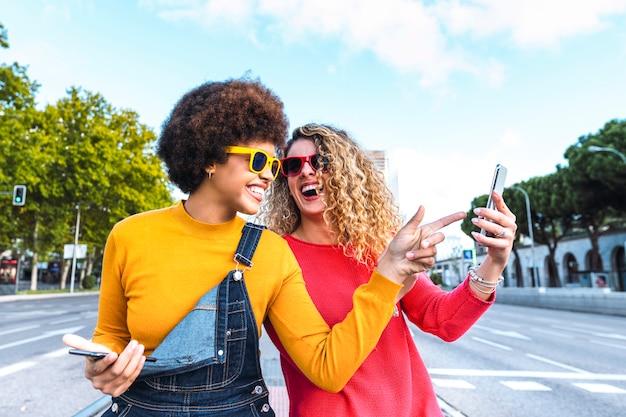 Przyjaciele za pomocą smartfona na ulicach miasta. koncepcja telefonii i komunikacji u młodych ludzi
