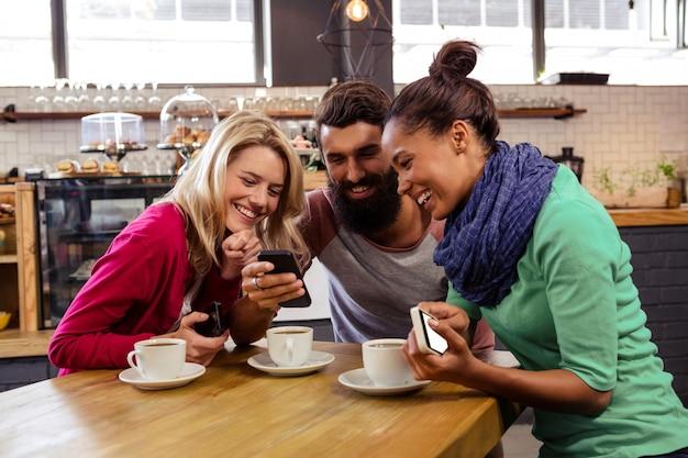 Przyjaciele za pomocą smartfonów siedzieć