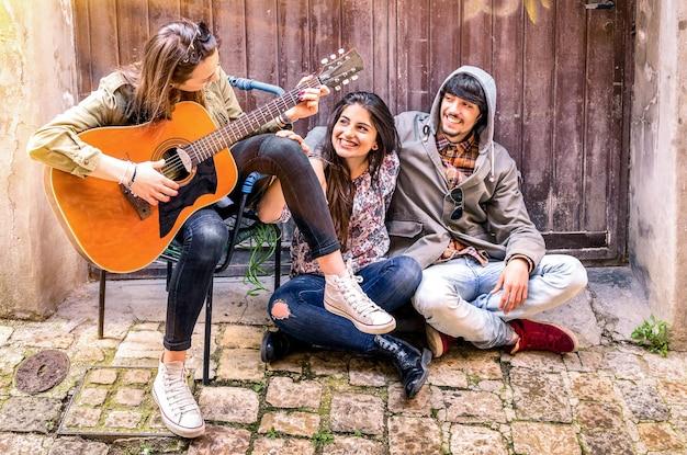Przyjaciele, zabawy razem grając na gitarze w domu na podwórku