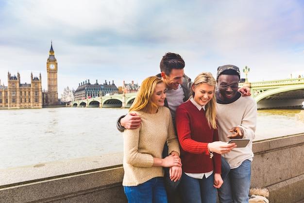Przyjaciele zabawy z smartphone w big ben w londynie