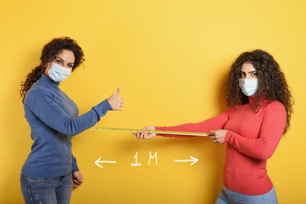 Przyjaciele zachowują między sobą odległość 1 metra. koncepcja zasad kodiv-19 w celu uniknięcia pandemii. żółty