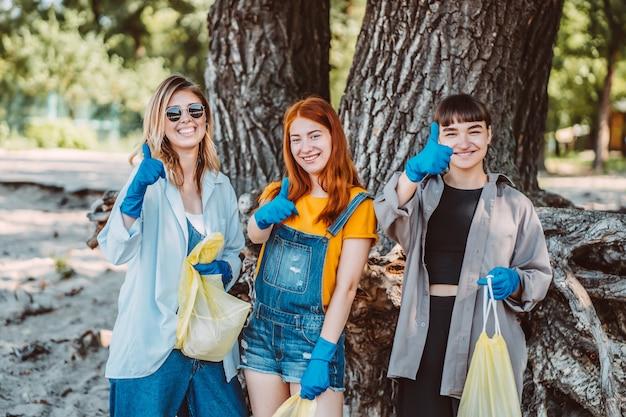 Przyjaciele zbierają śmieci z parku. dziewczyny pokazują kciuk do góry.
