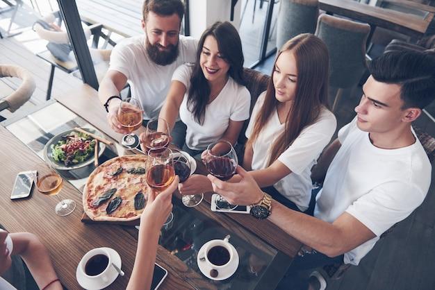 Przyjaciele zebrali się przy stole przy pysznym jedzeniu z kieliszkami czerwonego wina z okazji specjalnej okazji