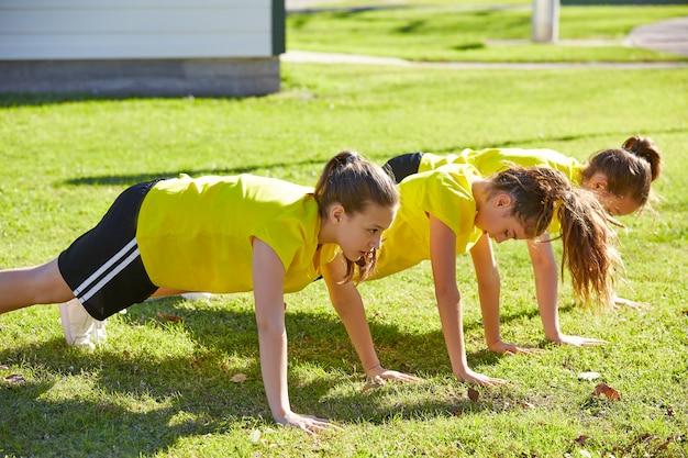 Przyjaciół dziewczyny nastolatki pompek trening w parku