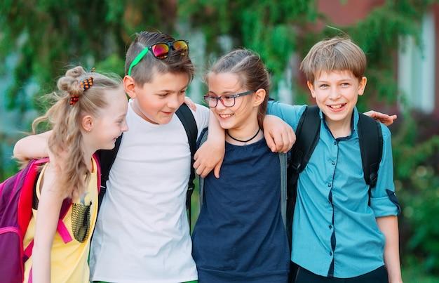 Przyjaźń dzieci. czworo małych uczniów, dwóch chłopców i dwie dziewczynki stoją w objęciach na boisku szkolnym.