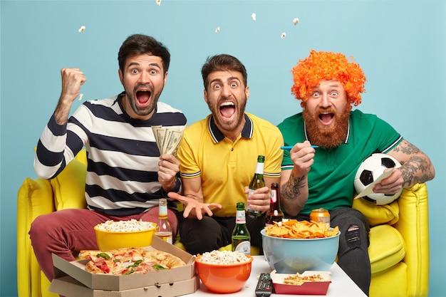 Przyjaźń, gra, hazard, koncepcja wypoczynku. emocjonalnie podekscytowani trzej przyjaciele płci męskiej oglądają w domu mecz piłki nożnej w telewizji, zaciskają pięści, krzyczą przy bramce
