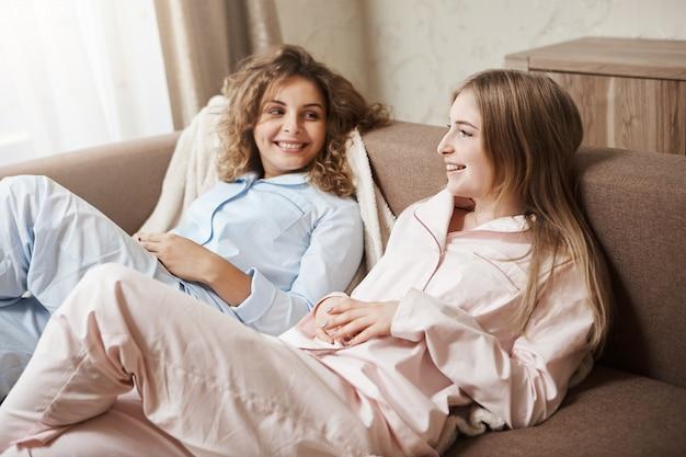 Przyjaźń jest przed związkiem. piękne europejskie dziewczyny leżące na kanapie w wygodnej bieliźnie nocnej, rozmawiające i bawiące się, dyskutujące o życiu i oglądające film w telewizji, spędzające wolny czas w domu
