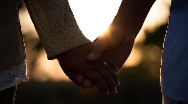 Przyjaźń miłość i walentynki koncepcja szczęśliwa para seniorów trzymająca się za rękę podczas zachodu słońca