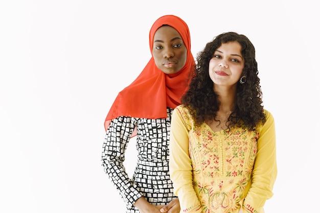 Przyjaźń narodów. afrykańskie i indyjskie kobiety w tradycyjnych strojach. odosobnione, białe studio.