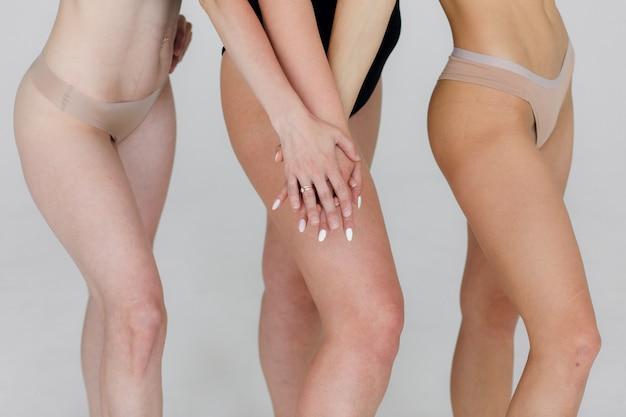 Przyjaźń piękna ciało pozytywne i koncepcja ludzi grupa szczęśliwych kobiet różnych w białej bieliźnie na różowym tle wysokiej jakości zdjęcie