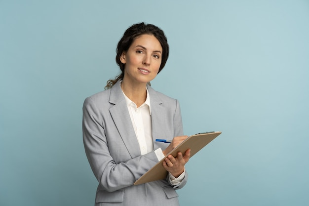 Przyjazna agentka ubezpieczeniowa kobieta nosi szary blezer i białą bluzkę trzymając schowek
