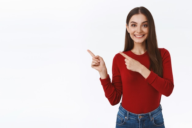 Przyjazna, asertywna ładna brunetka, która chętnie pokazuje promocję klienta, dobrą ofertę, wskazuje lewy górny róg, uśmiecha się szczęśliwa, pomaga osobie, która pyta o kierunek, stoi na białym tle